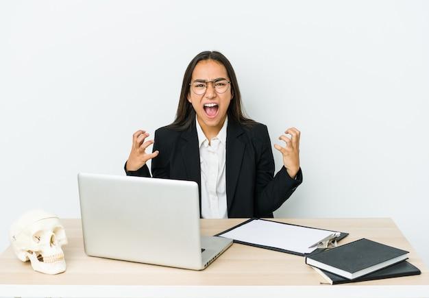 Giovane donna asiatica traumatologo isolata sul muro bianco che grida di rabbia.