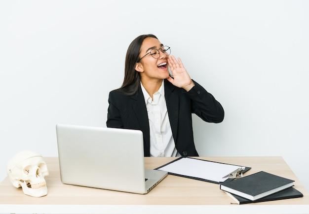 Giovane donna asiatica traumatologo isolata sul muro bianco che grida e che tiene il palmo vicino alla bocca aperta.