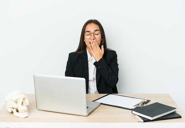 Giovane donna asiatica traumatologo isolata sul muro bianco che sbadiglia mostrando un gesto stanco che copre la bocca con la mano.