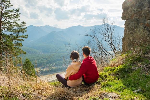 Coppia di giovani viaggiatori che riposano in montagna uomo e donna che fanno un'escursione con gli zaini