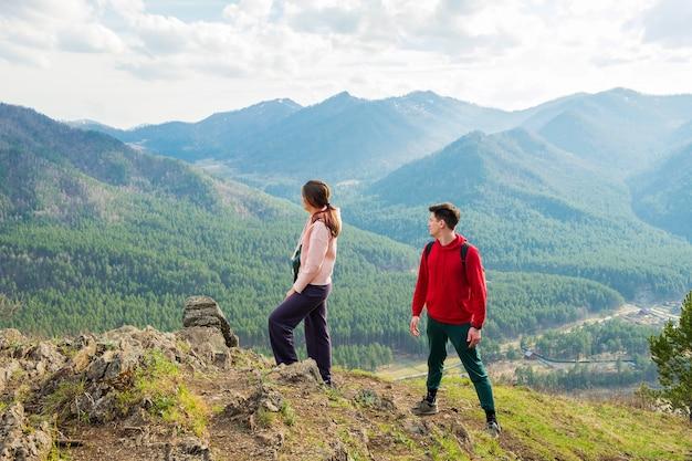 Una giovane coppia di viaggiatori sta in cima all'uomo e alla donna di montagna che fanno un'escursione con gli zaini