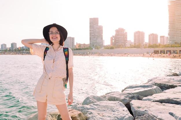 Sorridere della ragazza del giovane viaggiatore felice vicino al mare