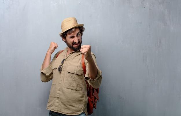 Giovane uomo viaggiatore o turista con una posa arrabbiata, aggressiva e minacciosa