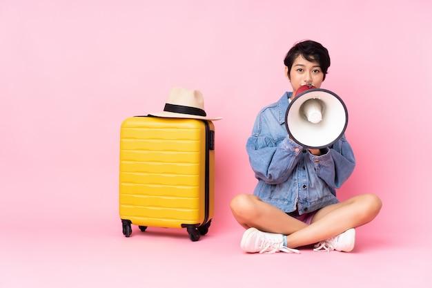 Donna vietnamita del giovane viaggiatore con la valigia che si siede sul pavimento sopra la parete rosa che grida tramite un megafono