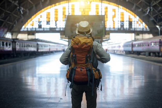Giovane viaggiatore che cammina con lo zaino sulla stazione ferroviaria e treno in attesa