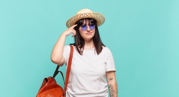 Donna giovane viaggiatrice che si sente confusa e perplessa mostrando che sei pazzo pazzo o fuori di testa