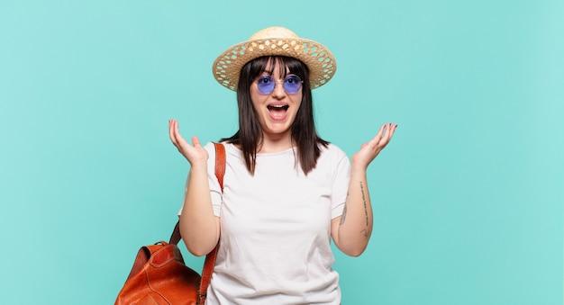 Donna giovane viaggiatore sentirsi felice eccitato sorpreso o scioccato sorridente e stupito per qualcosa di incredibile