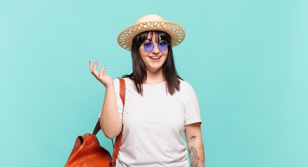 Donna giovane viaggiatore che si sente felice, sorpresa e allegra, sorridente con atteggiamento positivo, realizzando una soluzione o un'idea