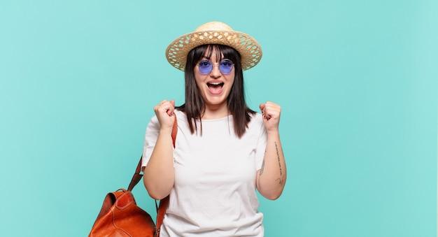 Donna giovane viaggiatore sentirsi scioccata, eccitata e felice, ridendo e celebrando il successo, dicendo wow!