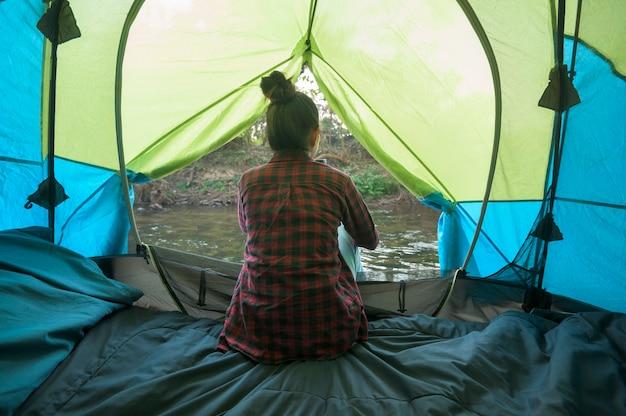 Una giovane donna viaggiatrice si diverte con la natura all'interno della tenda da campeggio