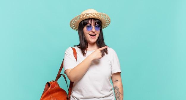 Donna del giovane viaggiatore che sembra eccitata e sorpresa che indica di lato e verso l'alto per copiare lo spazio