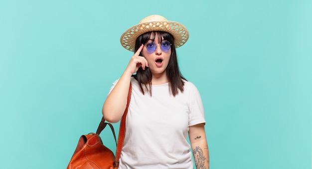 Donna giovane viaggiatore che sembra sorpresa, a bocca aperta, scioccata, realizzando un nuovo pensiero, idea o concetto