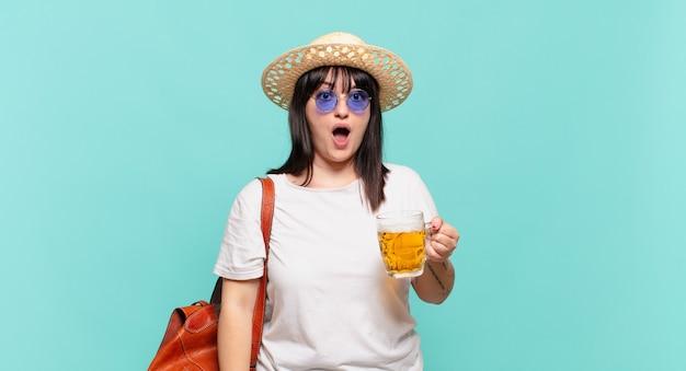 Donna giovane viaggiatore che sembra molto scioccata o sorpresa, fissando con la bocca aperta dicendo wow
