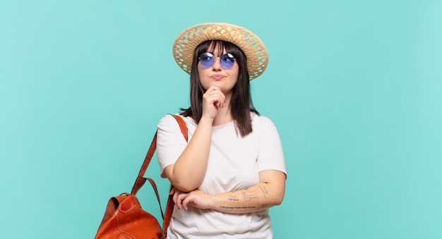 Giovane donna viaggiatore che pensa, si sente dubbioso e confuso, con diverse opzioni, chiedendosi quale decisione prendere