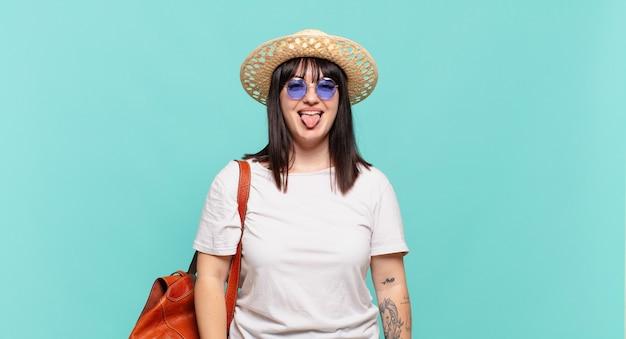 Donna giovane viaggiatrice con atteggiamento allegro, spensierato, ribelle, scherzando e con la lingua fuori, divertendosi