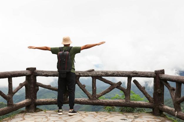 Viaggiatore con zaino e sacco a pelo di viaggio giovane che fa un'escursione nella bella foresta