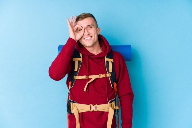 Uomo caucasico del giovane viaggiatore eccitato mantenendo il gesto giusto sull'occhio