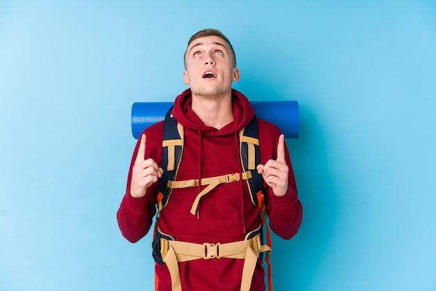 Uomo caucasico del giovane viaggiatore che indica a testa in giù con la bocca aperta.