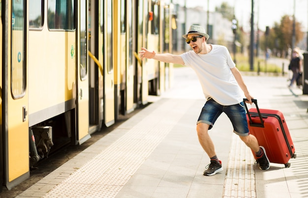 Uomo giovane viaggiatore in cappello e occhiali da sole con la valigia in esecuzione dalla stazione ferroviaria turista in ritardo durante il viaggio