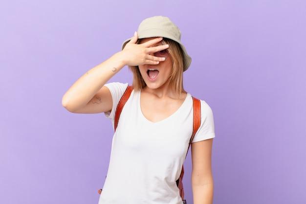 Giovane turista viaggiatore donna che sembra scioccato spaventato o terrorizzato che copre il viso con la mano