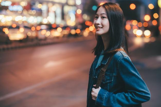 Donna giovane viaggiatore che cammina sulla strada della città di notte.