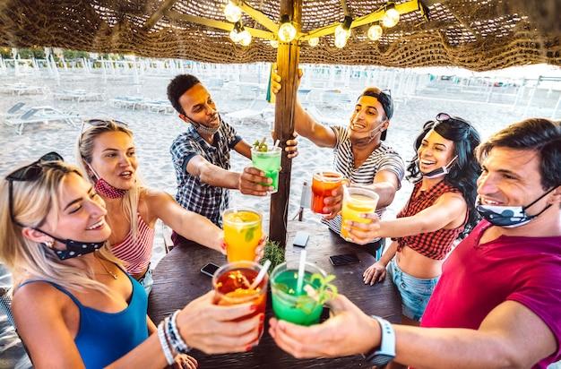 Giovani amici alla moda che tostano in spiaggia cocktail bar chiringuito con maschera