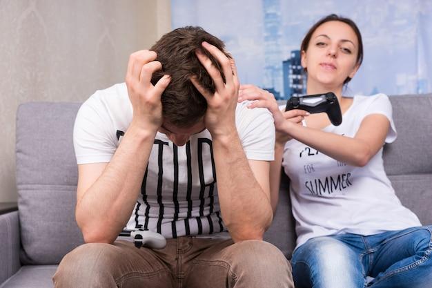 Ragazza giovane e alla moda che gongola dopo aver vinto un videogioco indicando suo marito con un sorriso mentre si tiene la testa per la vergogna e la frustrazione