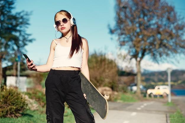 Ragazza giovane e alla moda con le cuffie e lo skateboard utilizzando il suo smartphone e in posa per la fotocamera. concetto di gioventù e hobby
