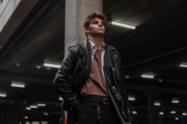 Il giovane hipster alla moda dell'uomo bello con l'acconciatura in una camicia vintage in un'elegante giacca di pelle nera in jeans alla moda sta riposando su una strada della città. modello di moda ragazzo attraente all'aperto.