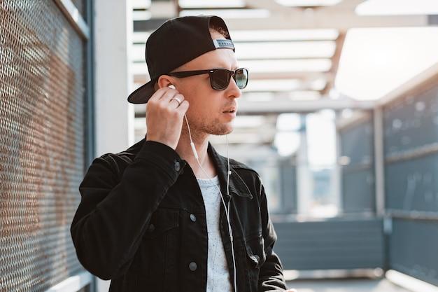 Un giovane ragazzo alla moda hipster con un berretto nero