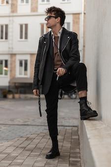 Il giovane hipster alla moda in abiti neri alla moda in occhiali da sole sta con una sigaretta in mano e si diverte a fumare vicino all'edificio sulla strada. un ragazzo attraente con un'acconciatura fuma in città.
