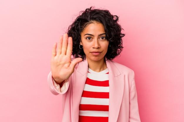 Giovane donna latina alla moda isolata su sfondo rosa in piedi con la mano tesa che mostra il segnale di stop, impedendoti.