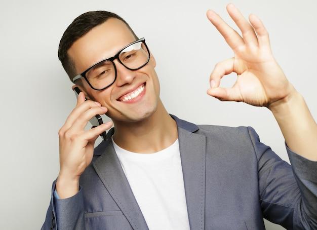 Giovane uomo alla moda che parla al cellulare, su sfondo bianco