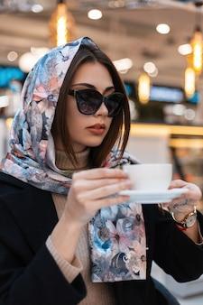 Giovane donna professionale alla moda con occhiali da sole scuri alla moda in elegante scialle di seta si gode il caffè mentre è seduta in casa. la modella attraente della ragazza di affari beve il cappuccino delizioso caldo in caffè