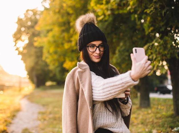 Blogger di giovane donna alla moda con caffè nel parco