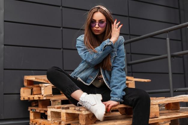 Hipster di giovane donna alla moda in occhiali viola giovanili in giacca di jeans blu alla moda in jeans neri in stivali di pelle bianca sta riposando su pallet di legno in città. ragazza moderna sexy all'aperto.