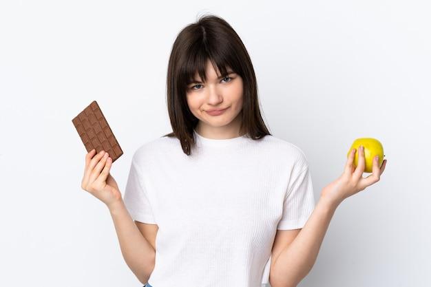 Giovane donna ucraina isolata sul muro bianco che ha dubbi mentre prende una tavoletta di cioccolato in una mano e una mela nell'altra
