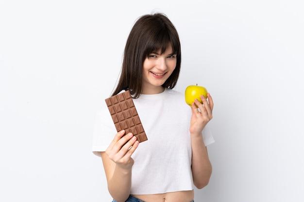 Giovane donna ucraina isolata sul muro bianco prendendo una tavoletta di cioccolato in una mano e una mela nell'altra