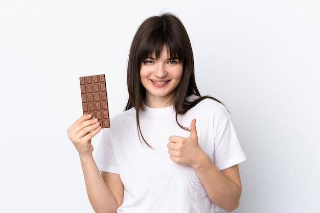 Giovane donna ucraina isolata sulla parete bianca che prende una compressa di cioccolato e con il pollice in su