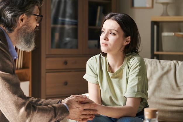 Giovane donna bruna infelice in abbigliamento casual che si siede sul divano davanti a uno psicologo professionista invecchiato tenendole le mani e sostenendola