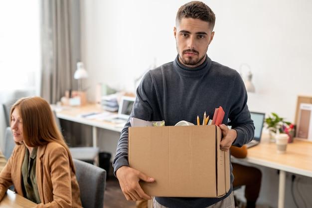 Giovane impiegato infelice che tiene scatola con forniture per ufficio