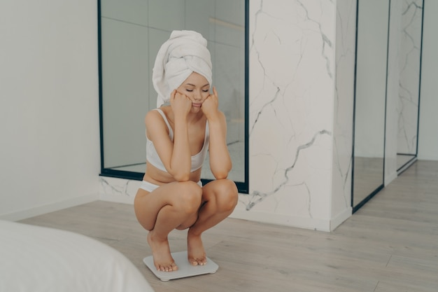 Giovane ragazza caucasica snella infelice accovacciata a piedi nudi su una bilancia elettronica con la faccia triste sulle mani nell'elegante interno della camera da letto, la femmina non poteva perdere peso durante la dieta