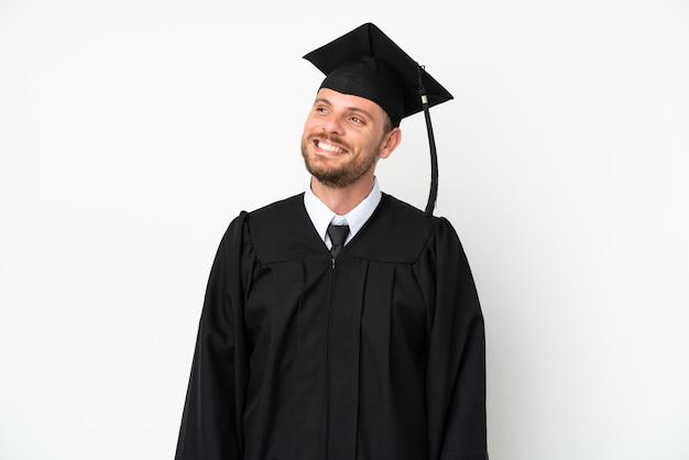 Giovane laureato brasiliano universitario isolato su sfondo bianco pensando a un'idea mentre guarda in alto