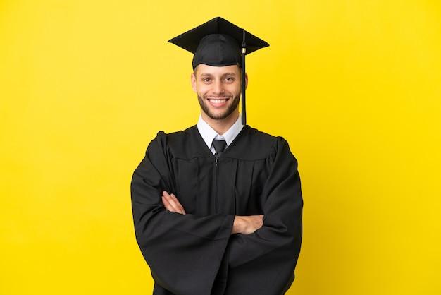 Giovane uomo caucasico laureato isolato su sfondo giallo tenendo le braccia incrociate in posizione frontale