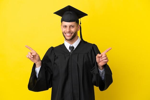 Giovane uomo caucasico laureato isolato su sfondo giallo che punta il dito verso i laterali e felice