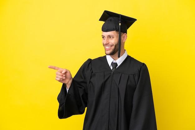 Giovane uomo caucasico laureato isolato su sfondo giallo che punta il dito sul lato e presenta un prodotto