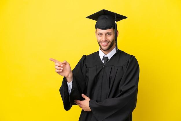 Giovane uomo caucasico laureato isolato su sfondo giallo che punta il dito a lato