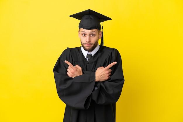 Giovane laureato uomo caucasico isolato su sfondo giallo che punta ai laterali che hanno dubbi