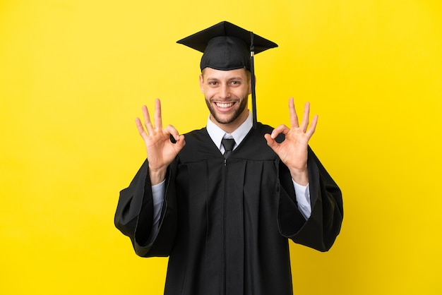 Giovane uomo caucasico laureato isolato su sfondo giallo che mostra un segno ok con le dita