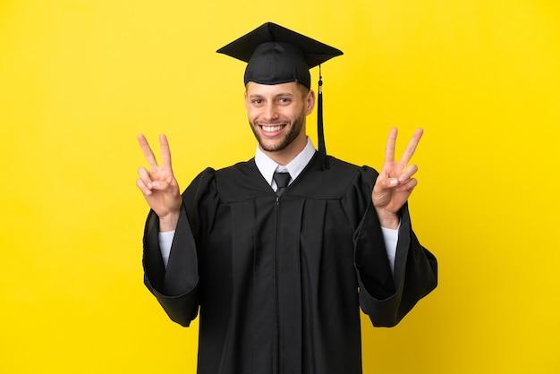 Giovane laureato uomo caucasico isolato su sfondo giallo che mostra il segno di vittoria con entrambe le mani